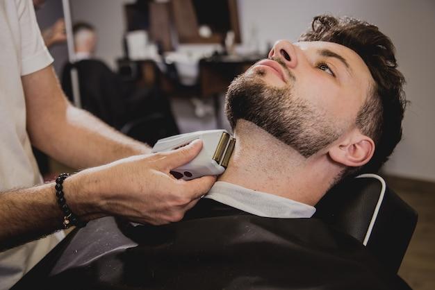 Młody człowiek z modną fryzurą w sklepie fryzjer. fryzjer robi fryzurę i brodę.