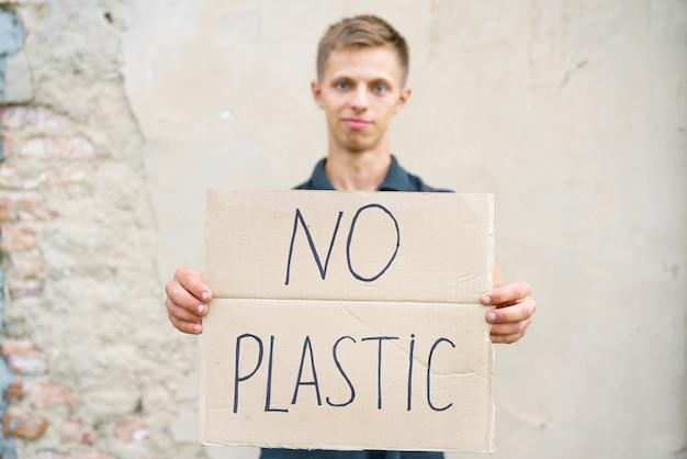 Młody człowiek z napisem na kartonie no plastikowy kaukaski facet na demonstracji przeciwko...