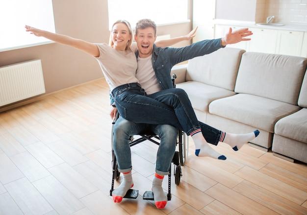 Młody człowiek z niepełnosprawnością i włączeniem gospodarstwa girlfirend na kolanach. uśmiechają się i pozują przed kamerą. wesoła szczęśliwa para.