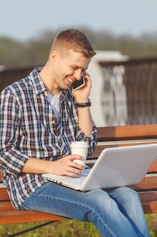 Młody człowiek z notatnikiem. koncepcja pracy zdalnej na zewnątrz