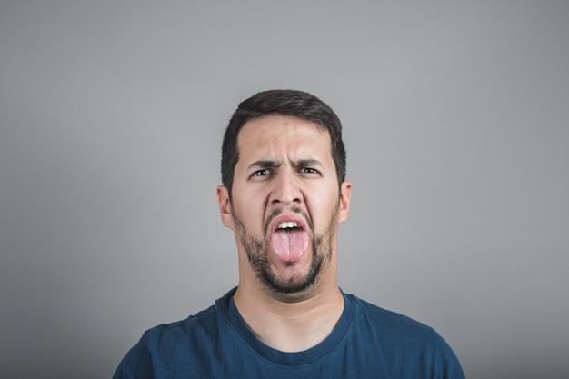 Młody człowiek z obrzydliwą twarzą wystaje mu język