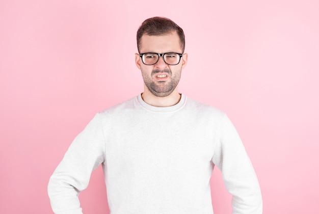 Młody człowiek z obrzydzeniem na twarzy na różowym tle