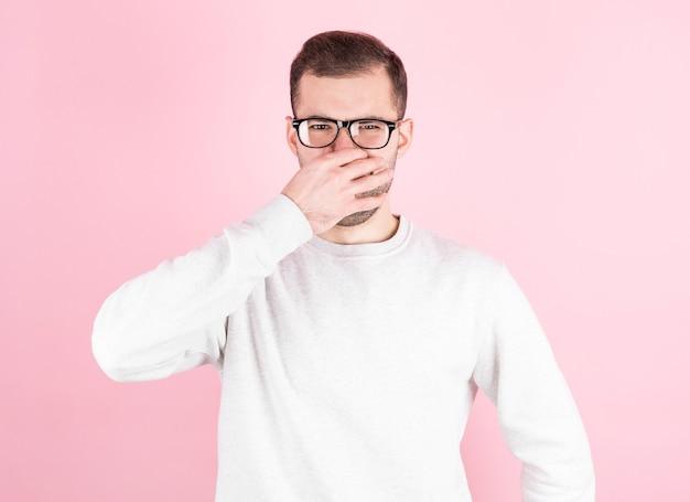 Młody człowiek z obrzydzeniem na twarzy szczypie nos na różowym tle.
