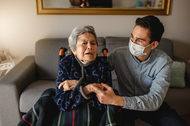 Młody człowiek z ochronną maską na twarz siedzi obok starej chorej kobiety w wieku na wózku inwalidzkim. rodzina, koncepcja opieki domowej.