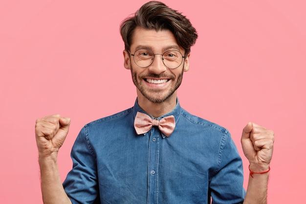 Młody człowiek z okrągłymi okularami i różową muszką