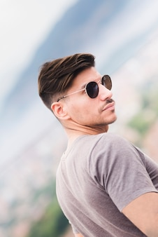 Młody człowiek z okularami przeciwsłonecznymi morzem