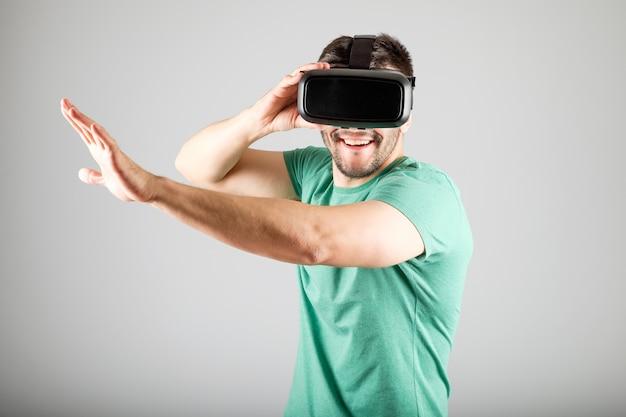 Młody człowiek z okularami wirtualnej rzeczywistości na białym tle