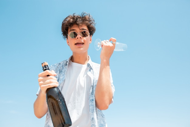 Młody człowiek z okulary i butelkę szampana