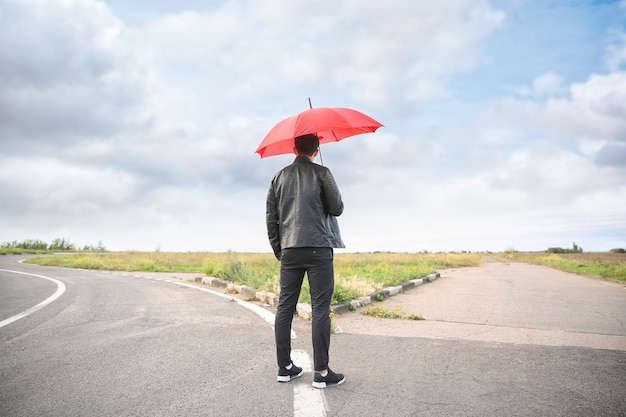 Młody człowiek z parasolem stojący na rozdrożu. koncepcja wyboru