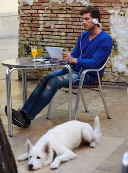 Młody człowiek z pastylka komputerem osobistym dotykiem z psem
