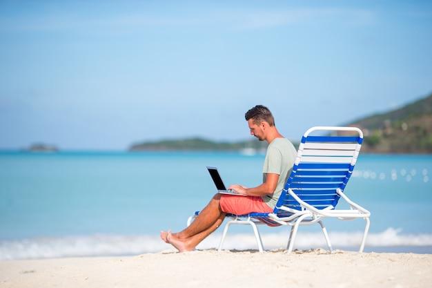Młody człowiek z pastylka komputerem podczas tropikalnego plaża wakacje