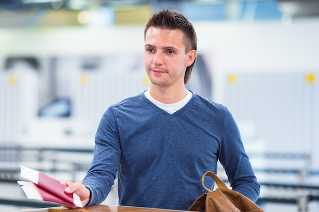 Młody człowiek z paszportami i kartami pokładowymi w recepcji na lotnisku