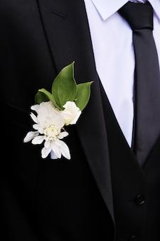 Młody człowiek z pięknym boutonniere białych róż lub chryzantem i zielonych liści, na klapie marynarki. pan młody w białej koszuli, krawacie, czarnym lub granatowym garniturze. motyw ślubu.