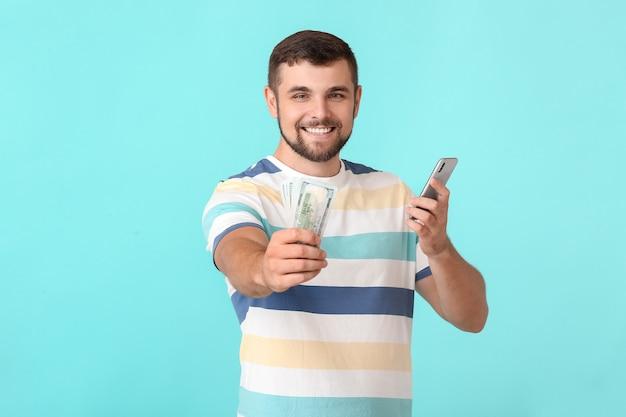 Młody człowiek z pieniędzmi i telefonem komórkowym na kolorowej powierzchni. koncepcja zakładu sportowego