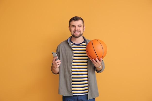 Młody człowiek z piłką i telefonem komórkowym na prange