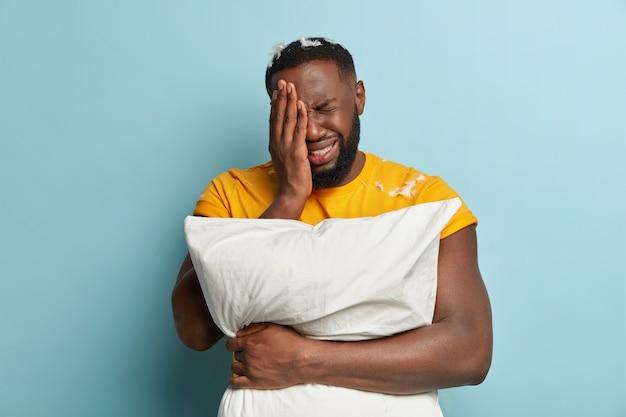 Młody człowiek z piór na koszulce trzymając poduszkę