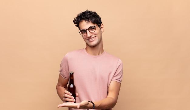 Młody człowiek z piwem uśmiecha się radośnie, czuje się szczęśliwy i pokazuje koncepcję w przestrzeni kopii z dłonią