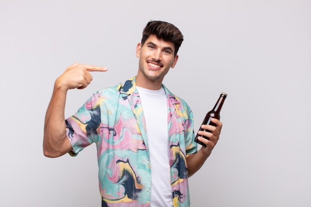 Młody człowiek z piwem, uśmiechnięty pewnie i wskazujący na swój szeroki uśmiech, pozytywne, zrelaksowane, zadowolone nastawienie