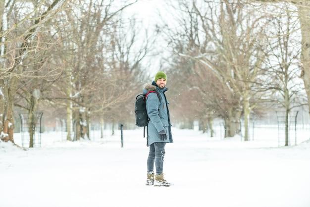 Młody człowiek z plecakiem na śniegu.