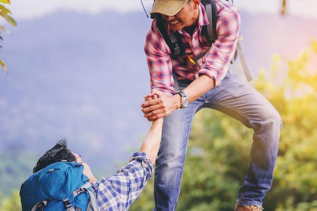 Młody człowiek z plecakiem pomaga przyjaciela wspiąć się na szczyt góry.