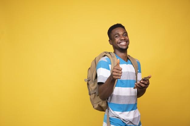 Młody człowiek z plecakiem robi gest kciuk w górę podczas korzystania z telefonu