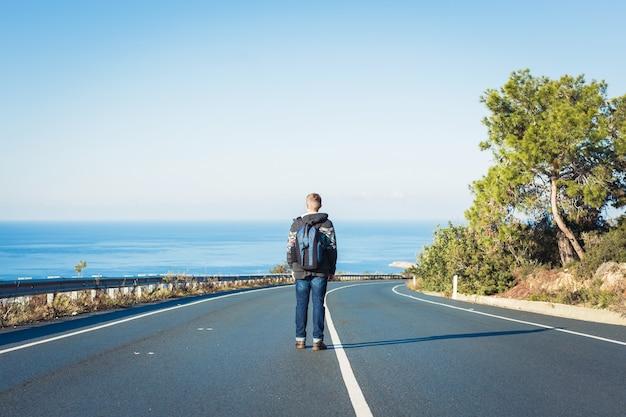 Młody człowiek z plecakiem samotnie spaceruje po drodze. koncepcja podróży