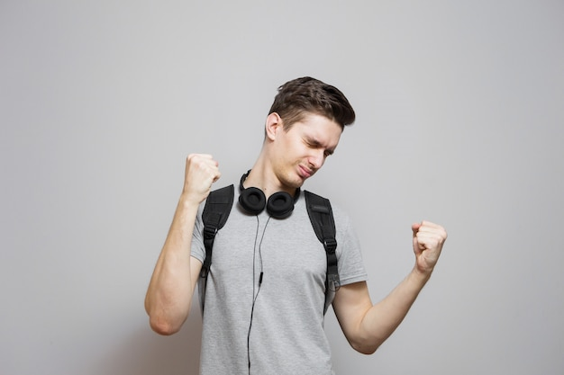 Młody człowiek z plecakiem w hełmofonach na szarym tle. student z torbą słucha muzyki.