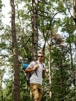 Młody człowiek z plecakiem w lesie
