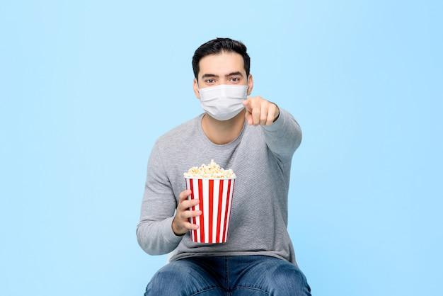 Młody człowiek z popkornem chroń się, nosząc medyczną maskę na twarzy, jednocześnie ciesząc się oglądaniem filmu na białym tle