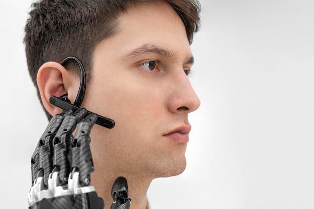 Młody człowiek z prototypem dłoni aktywującym słuchawki bluetooth