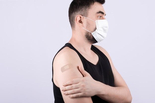 Młody człowiek z przylepnym bandażem na ramieniu po szczepieniu koronowym