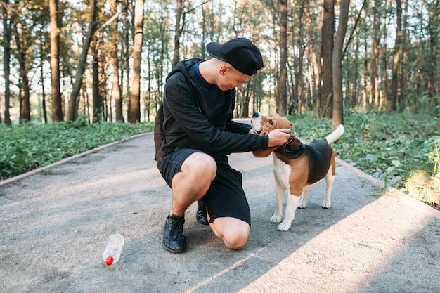 Młody człowiek z psem na wiejskiej drodze w lesie.