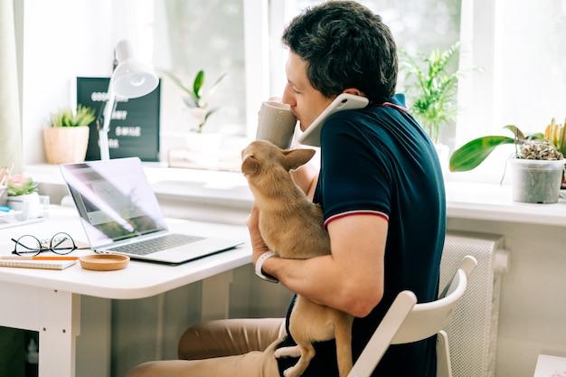Młody człowiek z psem pracuje w domu