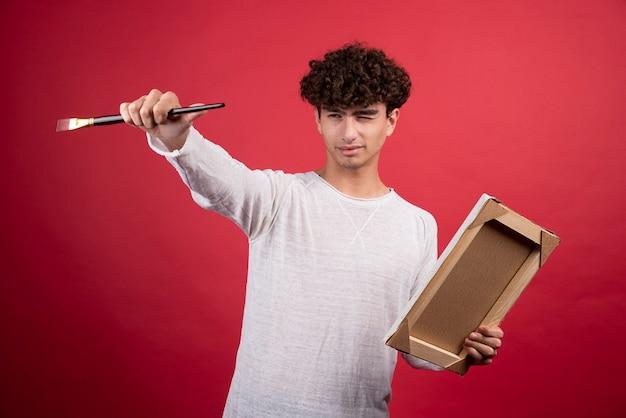 Młody człowiek z pustym płótnem i pędzlem próbuje dowiedzieć się, co namalować.