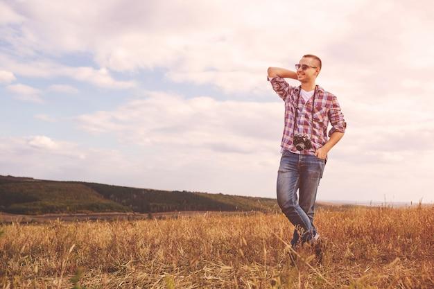 Młody człowiek z retro aparat fotograficzny hipster zewnątrz stylu życia