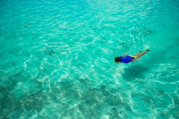 Młody człowiek z rurką w czystych tropikalnych turkusowych wodach