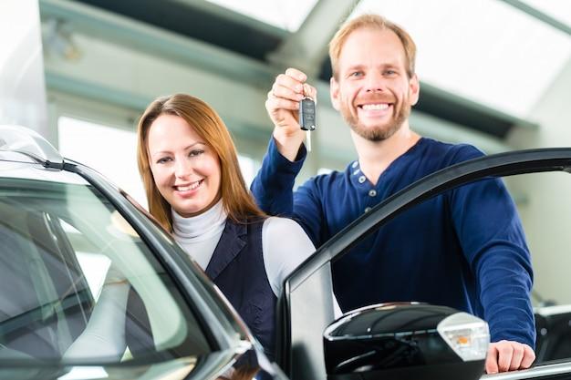 Młody człowiek z samochodem w przedstawicielstwie firmy samochodowej