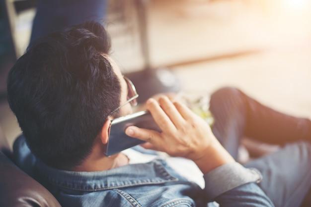 Młody człowiek z smartfon uśmiecha relaks w kawiarni.