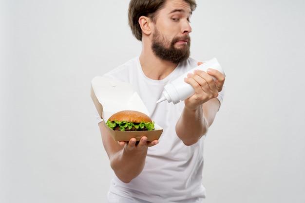 Młody człowiek z soczystego hamburgera w ręce