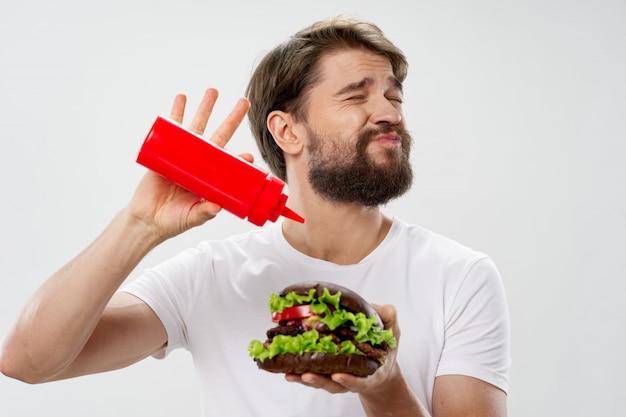 Młody człowiek z soczystego hamburgera w ręku, dodając keczup