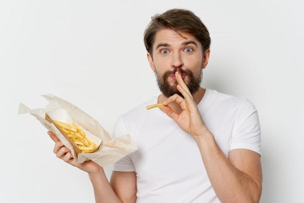 Młody człowiek z soczystym hamburgerem w rękach, mężczyzna jedzący burgera