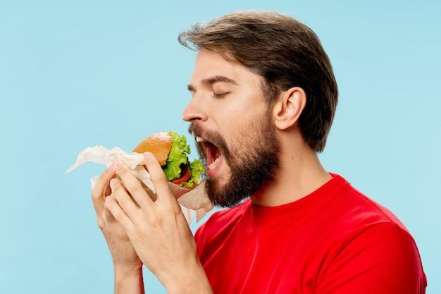 Młody człowiek z soczystym hamburgerem w ręku, mężczyzna jedzący burgera
