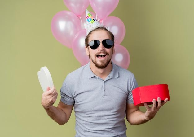 Młody człowiek z świąteczną czapką świętuje urodziny trzymając pudełko szczęśliwy i podekscytowany, uśmiechnięty wesoło stojąc z balonami nad jasną ścianą