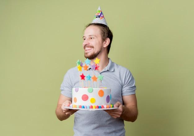 Młody człowiek z świąteczną czapką trzyma tort urodzinowy obchodzi przyjęcie urodzinowe szczęśliwy i podekscytowany nad jasną ścianą