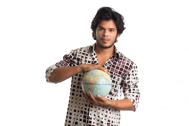 Młody człowiek z światową kulą ziemską na białym tle.