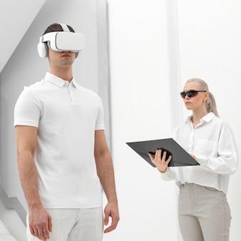 Młody człowiek z symulatorem wirtualnej rzeczywistości i testowaniem kobiety