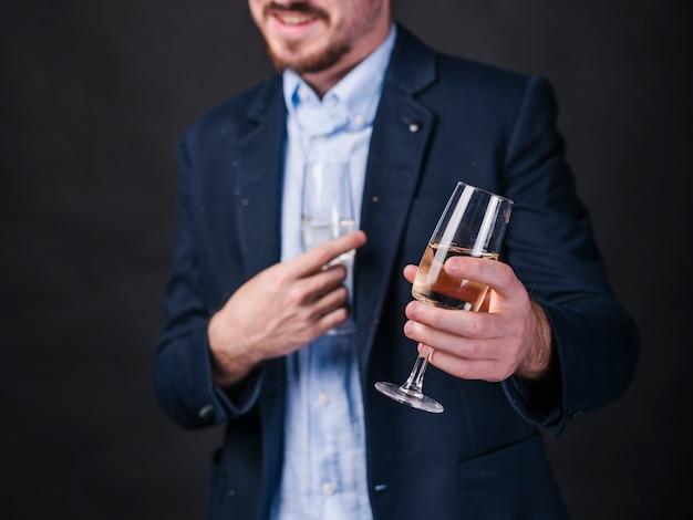Młody człowiek z szampańskimi szkłami w rękach