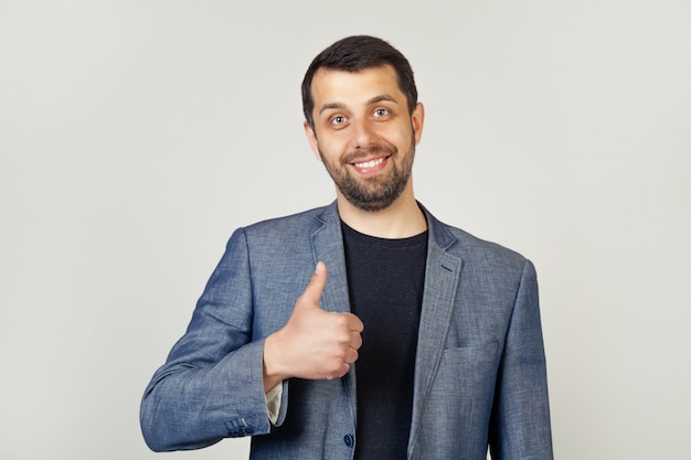 Młody człowiek z szczecina biznesmena seansu palcem up z szczęśliwym uśmiechem
