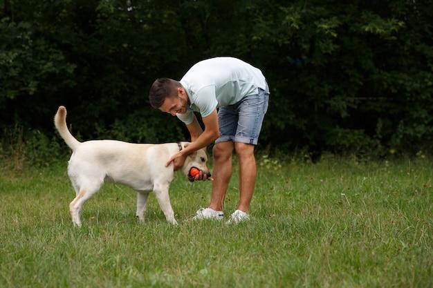 Młody człowiek z szczęśliwym labradorem w parku