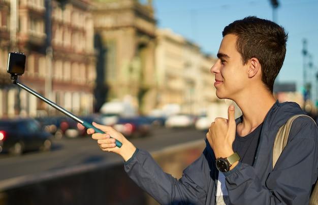 Młody człowiek z telefonem jest na ulicy dużego miasta i kciuki do góry, blogger